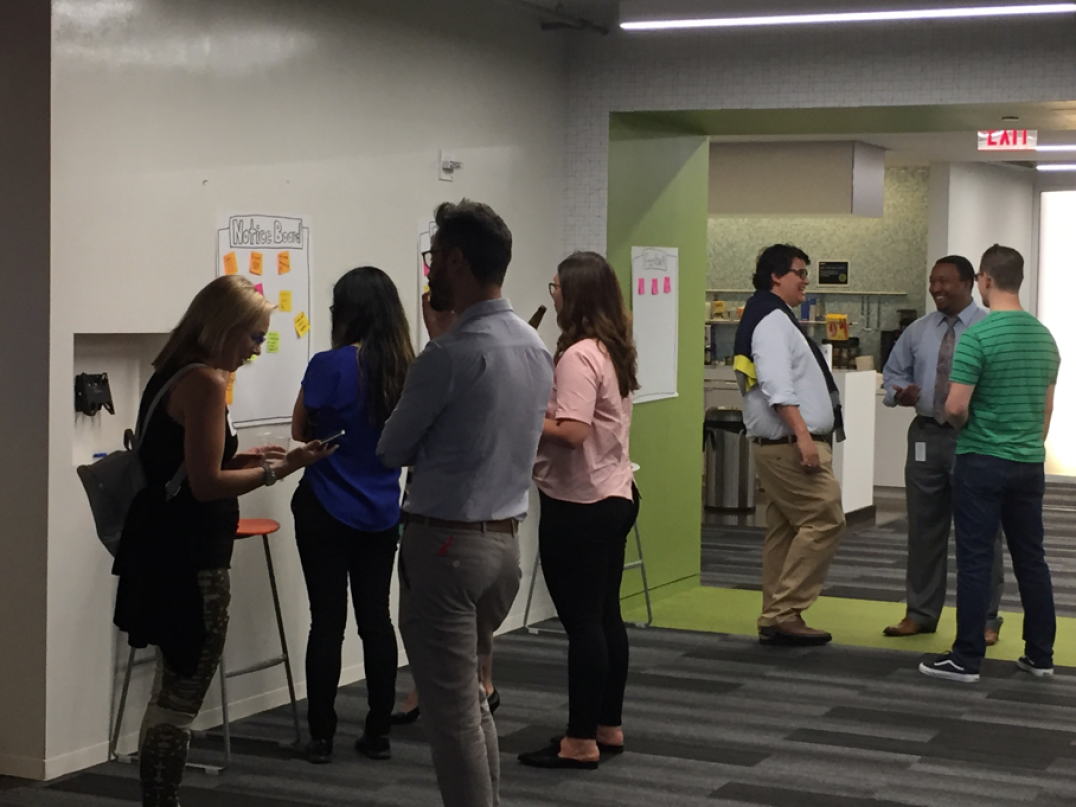 Service Designers huddle around the Notice Board and hang out at Deloitte Digital.